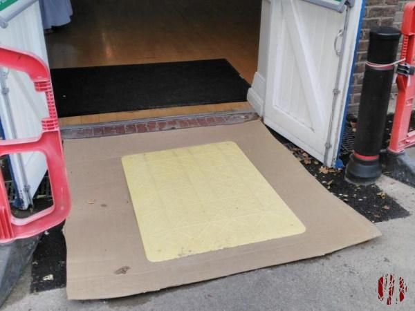 A large piece of cardboard spanning an area of soft tarmac.