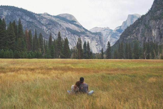 A couple sat leaning on each other in the way of a view of the forest and mountains behind