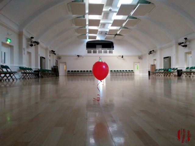 A helium party balloon at a point of equilibrium just above the wooden floor of the Drill Hall
