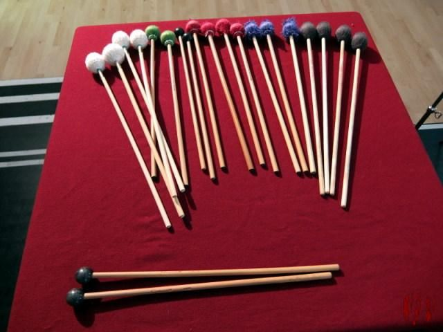About a dozen pairs of percussion mallets of different types on top of a square table with darkish red table cloth.