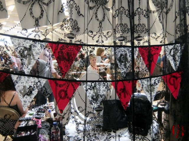A woman combing a girl's hair seen through one panel of an elaborately decorated lace curtain.
