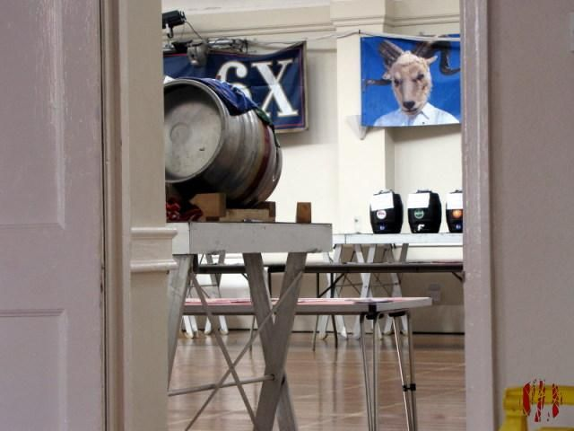Looking through a doorway at the Drill Hall laid out for a beer festival with part of an advertising banner in view with a rams head on a human body looking towards the camera