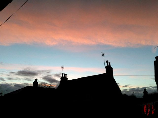 The dark silhouette of roof tops with chimneys and television aerials against a bright blue sky with white clouds above coloured orange by the setting sun