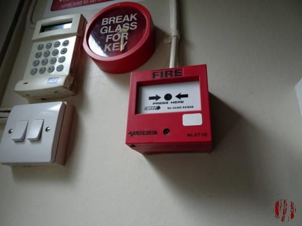 A fire alarm call point or break glass seen in close up from odd angles.