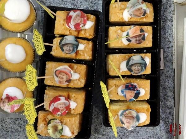 Photographs of the Queen of England on edible paper stuck on small cakes with a little crown on a stick with 90 on it to commemorate her birthday.