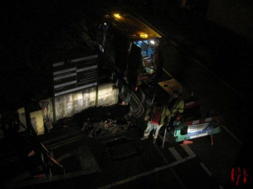 Men in a hole looking repairing a gas leak during the night as seen from above.