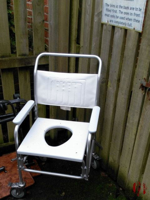 A seat with wheels with a hole in it for certain biological functions lacking a full set of wheels.