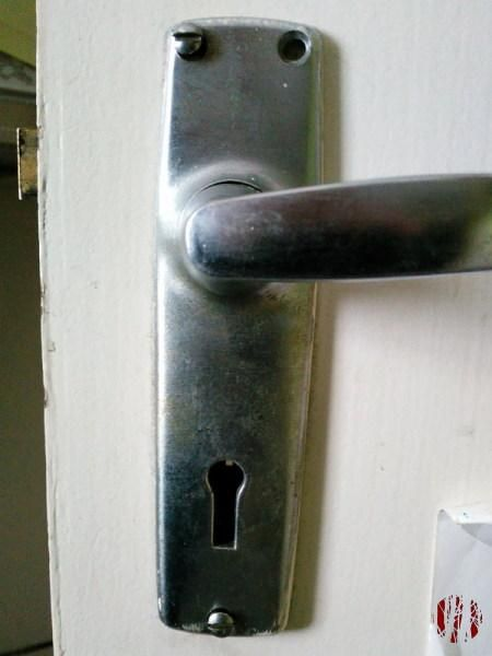 Door handle held on with only two of the possible screws and at an odd angle.