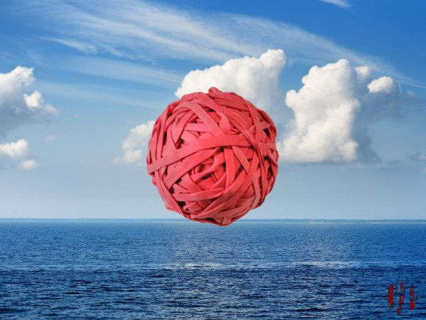 A ball of elastic bands floating amongst clouds in blue sky above ocean. No I don't know why either.