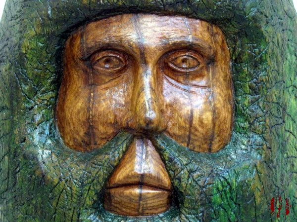Large wood carving of a face with an inordinate amount of green hair and whiskers.