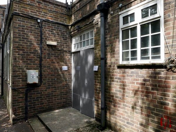 A mottled effect of shadows of trees against the brick wall, plastic framed windows, and newly painted grey fire exit doors of one side of the Drill Hall Horsham.