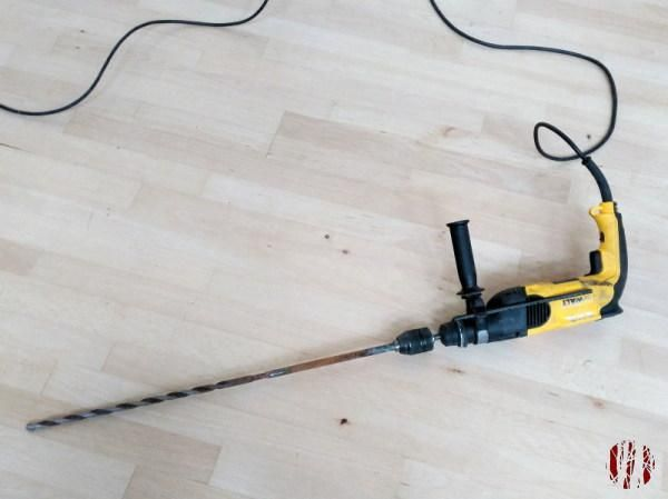 Yellow and black DeWalt power hammer drill with extremely long drill bit to make a hole in a very thick wall.