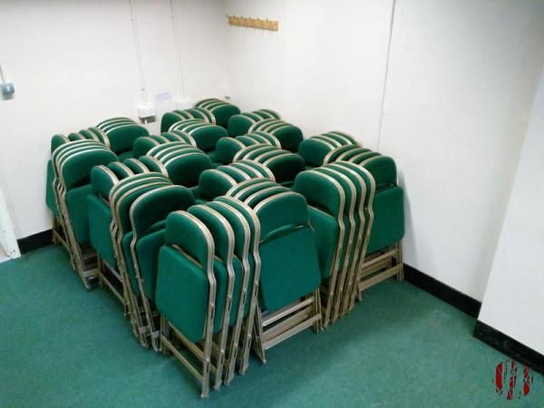 Folding chairs stacked in fours frame against frame to avoid crushing the foamed sit creating a geometric pattern.