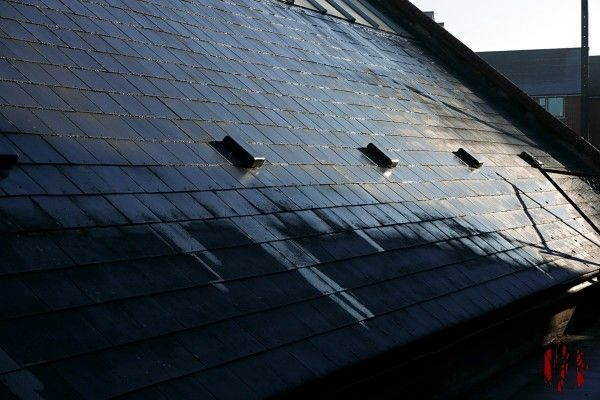 Photo of the sun shining on the partially wet black slate roof of a large community hall.