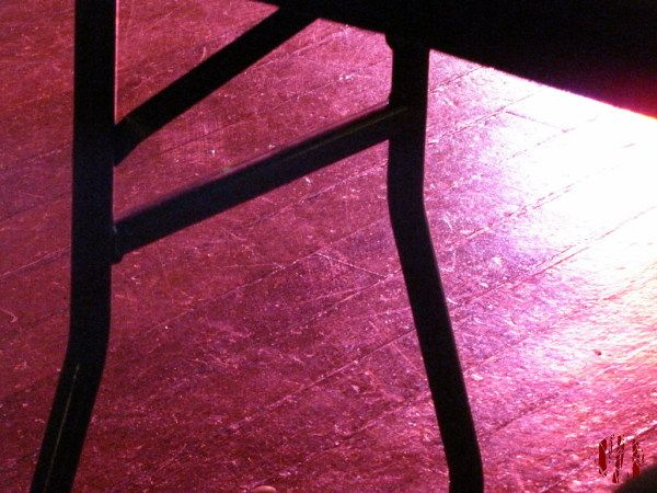 Part of the top and legs of a table in silhouette with the floor below it lit in colour by disco lighting