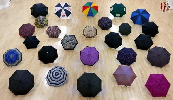 Twenty-six umbrellas from small to large laid out in the Drill Hall seen from above and in front.