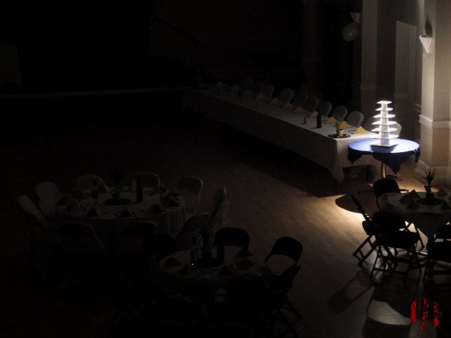 A multi-layered cake stand lit from above and behind in an otherwise dark hall laid out for a wedding reception
