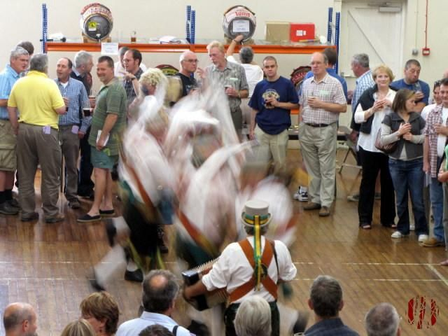 A blur of Morris Men dancing at a beer festival whilst those looking on are in focus