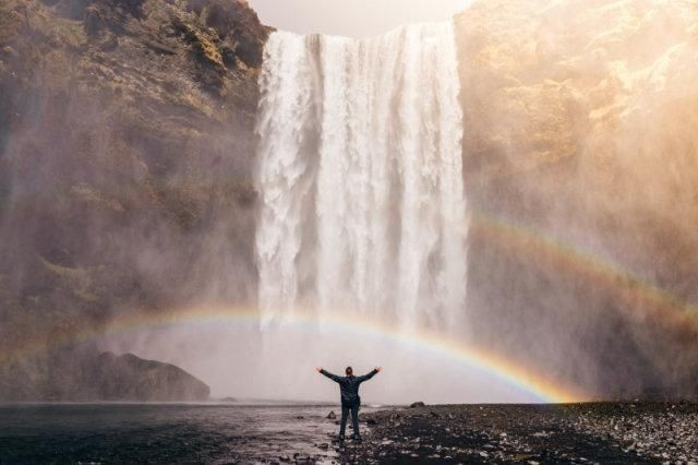 A double rainbow forming around a waterfall with some wally in front with hsi arms outstretched