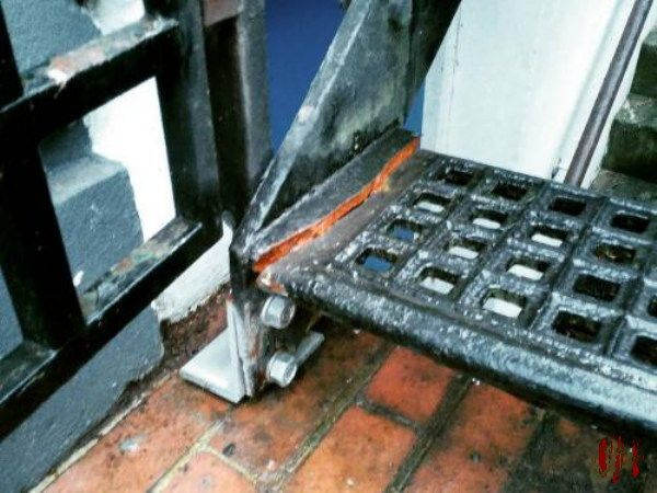 A photograph of a metal staircase showing a step broken whilst a foot was replaced.