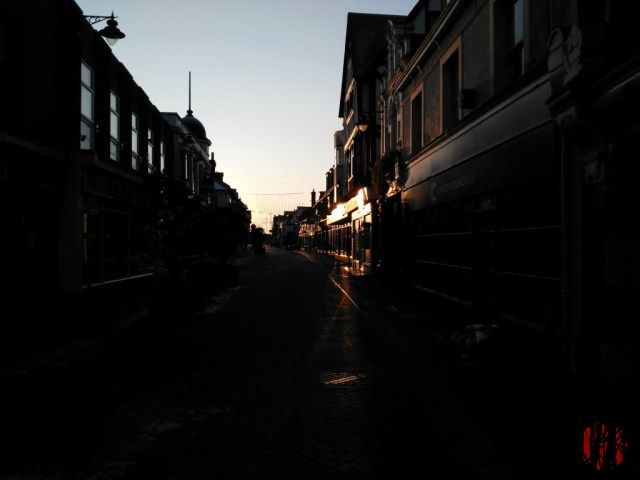 The sun shining from a low angle on fascia boards on an otherwise dark street early in the morning
