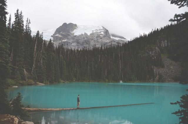 A man stood by a blue mountain lake spoiling the vista