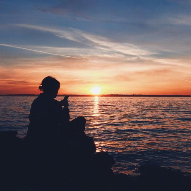 A young woman sits playing with her phone on rocks beside the sea whilst a beautiful sunset takes place behind her