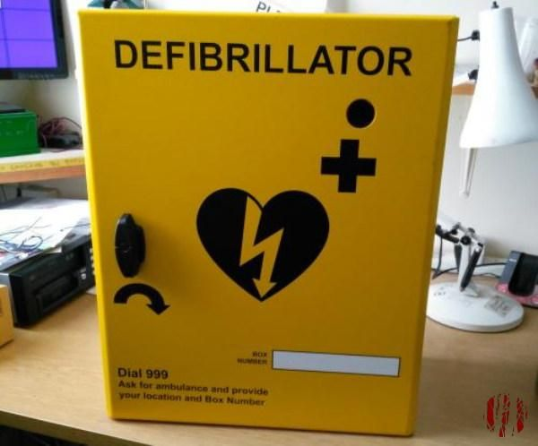 A very yellow metal cabinet for a defibrillator with a heart in black on the front with a lighting rod passing through it.