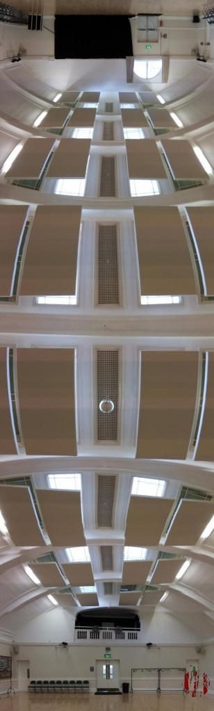 Panoramic view of the main hall of the Drill Hall in Horsham from one end to the other via the arched roof with hanging acoustic panels and at its centre point a mirror ball.