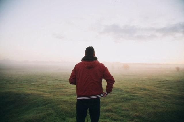 A man stood in front of grassland in the morning mist
