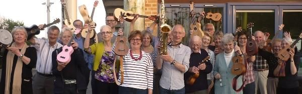 A photograph of twenty or so mainly senior citizens holding aloft ukeleles except one man with a saxophone.