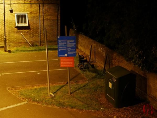 Late at night under artificial light a abandoned wheelchair is photographed on the grass next to a car park bay