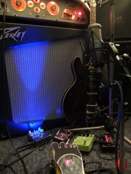 A guitar propped against an amplifier with several guitar pedals in the foreground.