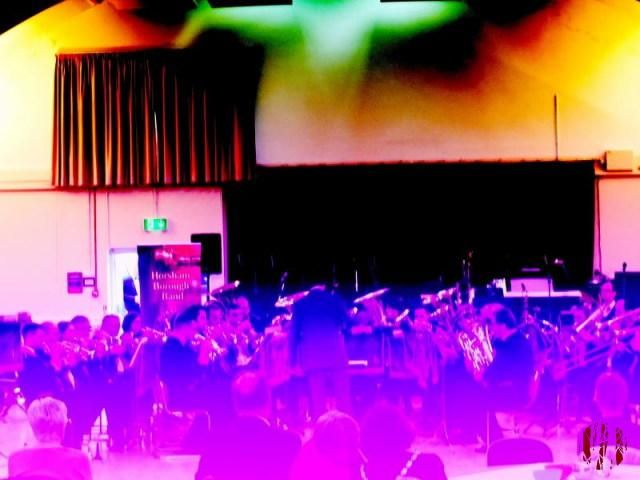 Photograph of a brass band taken with a broken camera resulting in odd colours.