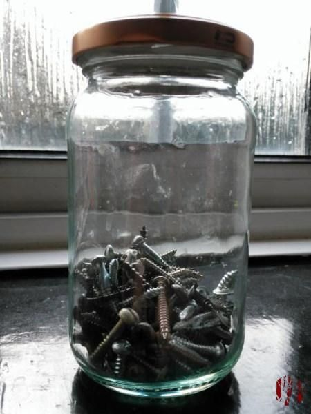 A close up of a jar of miscellaneous screws. Round head, medium length, general purpose.