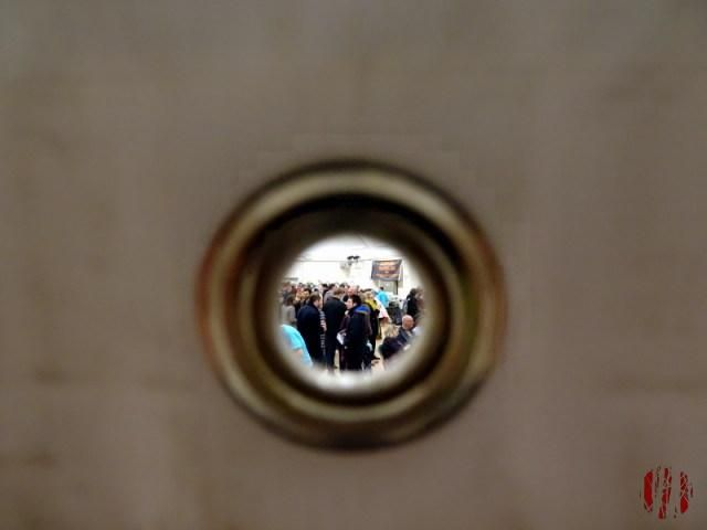The crowd at a beer festival seen through the small round eyelet in an advertisting banner.