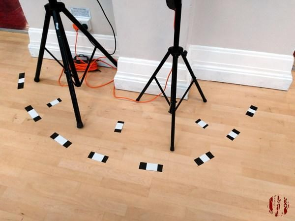 Lighting and speaker stands near a wall with a neat semi-circle of D.I.Y. black and white gaffer tape warning markings.