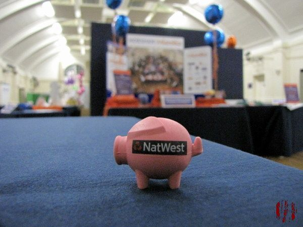 Tiny pink Natwest Pig on a table at a business show with stands behind