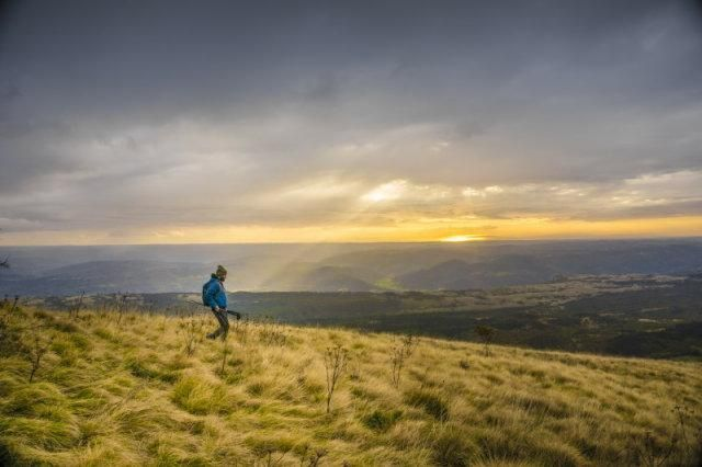Man carrying a tripod walking into a shot of grassy hills with shafts of sunlight coming through clouds behind