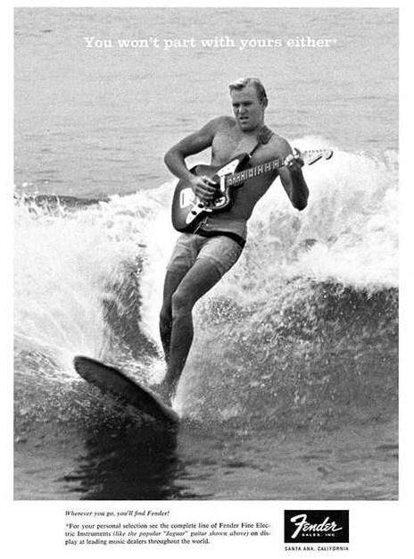 A man surfing whilst playing a Fender guitar