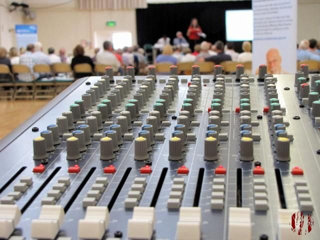 Looking across a Soundcraft L7 Mark II mixing desk towards a presentation which is artistically our of focus, if I do say myself