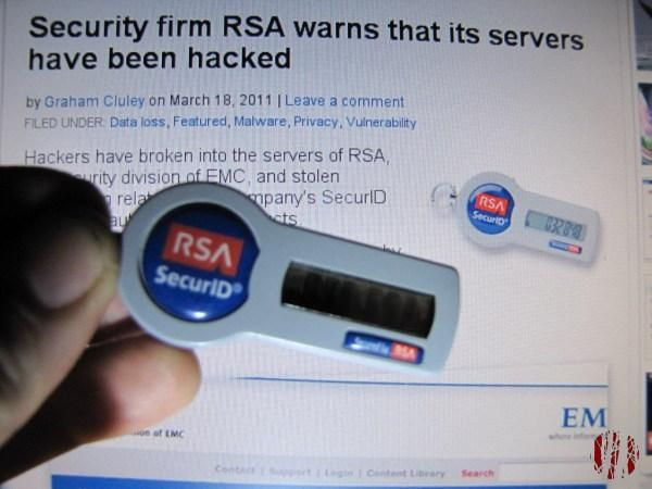 Me holding an RSA security keyfob in front of a computer screen showing that the same item in an article about the RSA servers having been hacked.