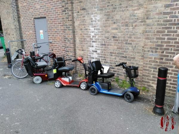 Several Electric mobility buggies lined up at an angle at the back of the Drill Hall.