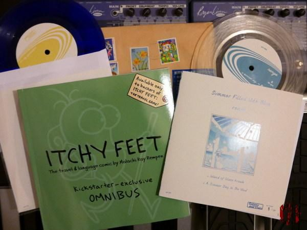 Two singles in coloured vinyl by Renge of Japan and a book of Itchy Feet travel comics.