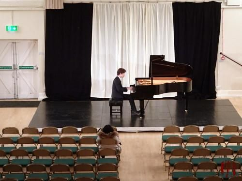 A pianist playing in front of rows of seats all empty except for one… Whilst rehearsing.