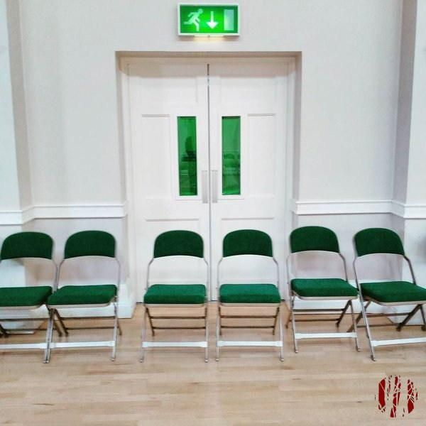 A fire exit blocked by chairs.