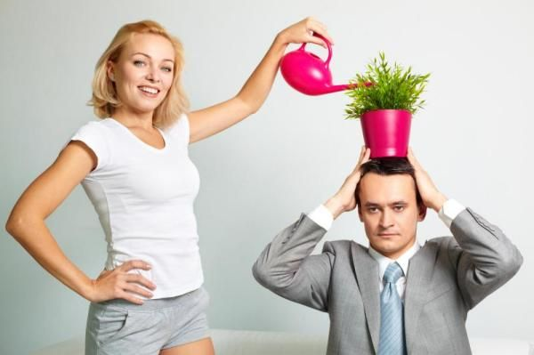 Photo Of Serious Man With Plant On Head Being Watered By Happy Woman - I couldn't tell you why.