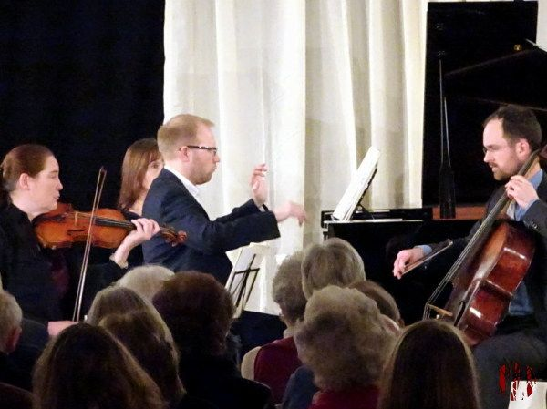 A piano trio with eponymous pianist flapping his hands about in the air above the keyboard.