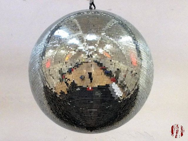 The Drill Hall Horsham laid out for dancing with tables around the sides as seen reflected in a mirror ball hung above the stage at one end.