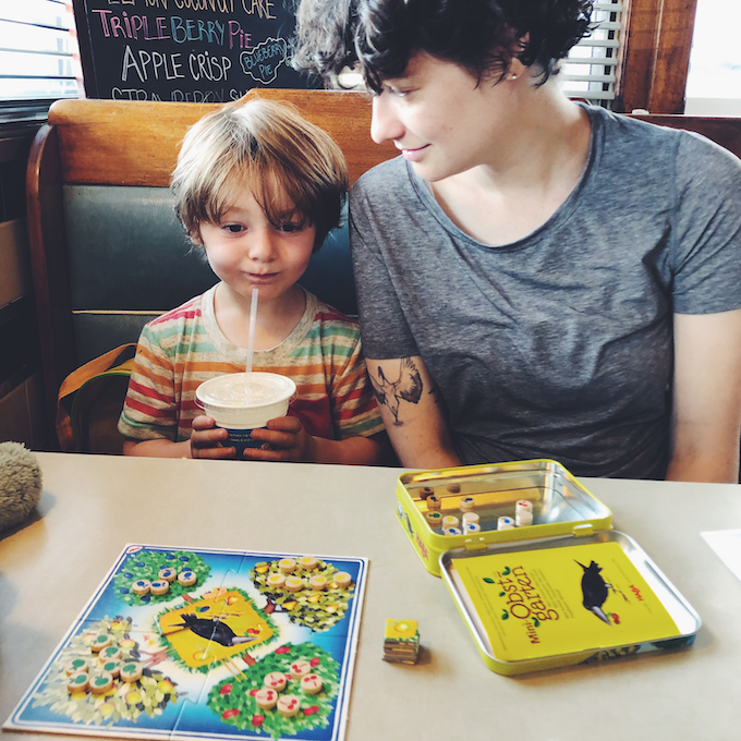 Kid and parent with curly hair playing a board game at a diner.
